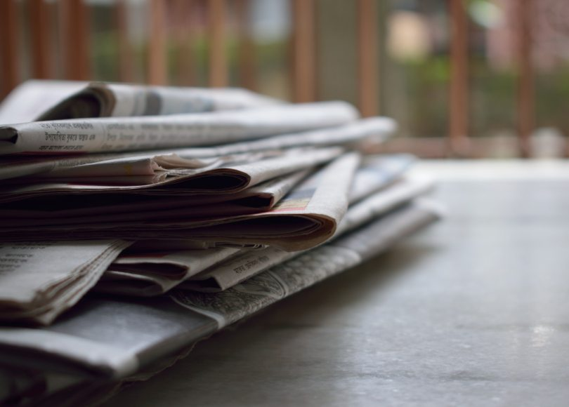 Pexels - A stack on newspapers on a table in front of a window