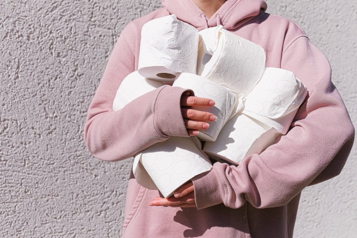 Pexels - A woman in a pink hoodie holds multiple rolls of toilet paper