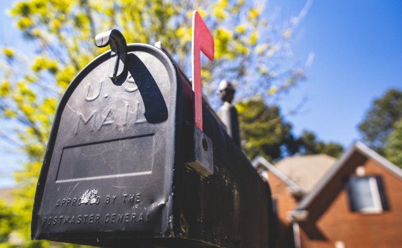 Pexels - Closeup of a black mailbox in front of a suburban house