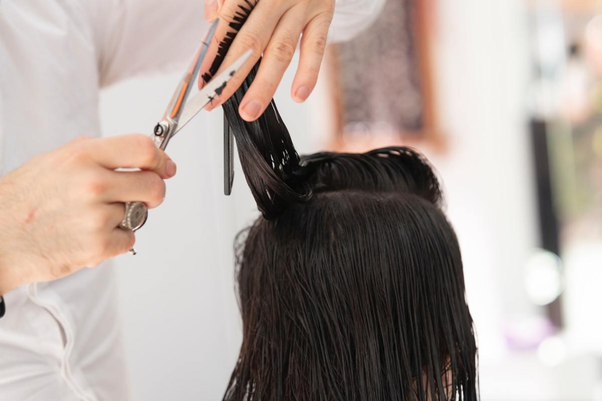 Pexels - A person cutting a woman's hair