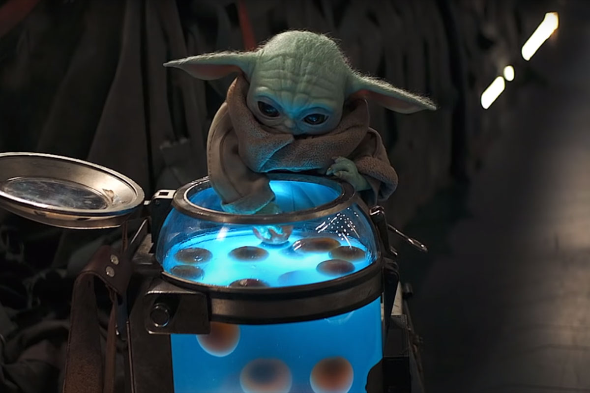 Screencap from S2, Ep. 2, The Mandalorian: Baby Yoda eating the Frog Lady's eggs from their container tank.