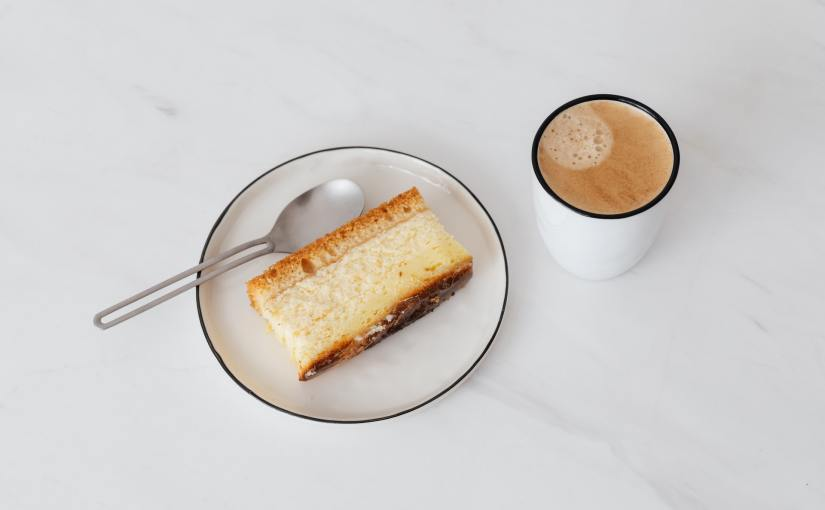 Pexels - Coffee and a piece of cake on a white table.