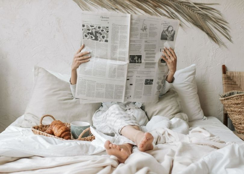 Pexels - A woman, in bed, reading a newspaper, with the paper held up in front of her face.